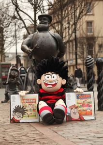 Dennis the Menace poses with an enlarged version of the new Beano stamp in front of the Desperate Dan statue in Dundee-765443